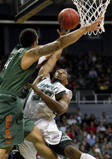 CORRECTS TEAM AND NAME OF PLAYER TO JONES - Miami guard Trey McKinney Jones (4) attempts to block a shot by Hawaii guard Brandon Spearman, right, in the first half of an NCAA college basketball game in the Diamond Head Classic Saturday, Dec. 22, 2012, in Honolulu. (AP Photo/Eugene Tanner)