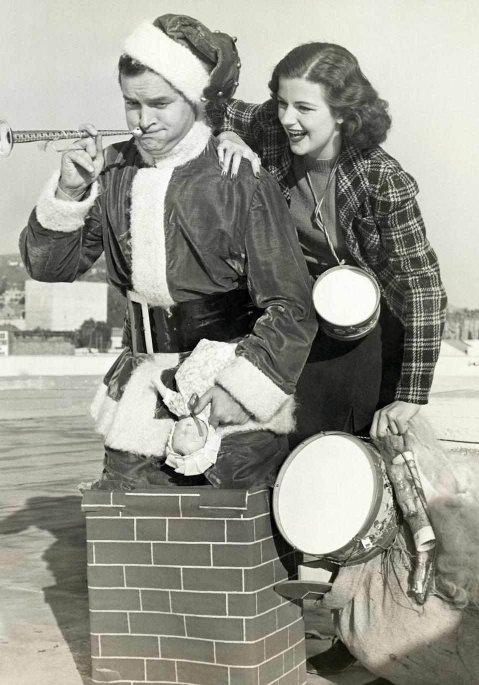<p>Radio star and comedian Bob Hope conjures up a few laughs from actress Helen Wood as he acts like Santa Claus for an event on December 12, 1938. </p>