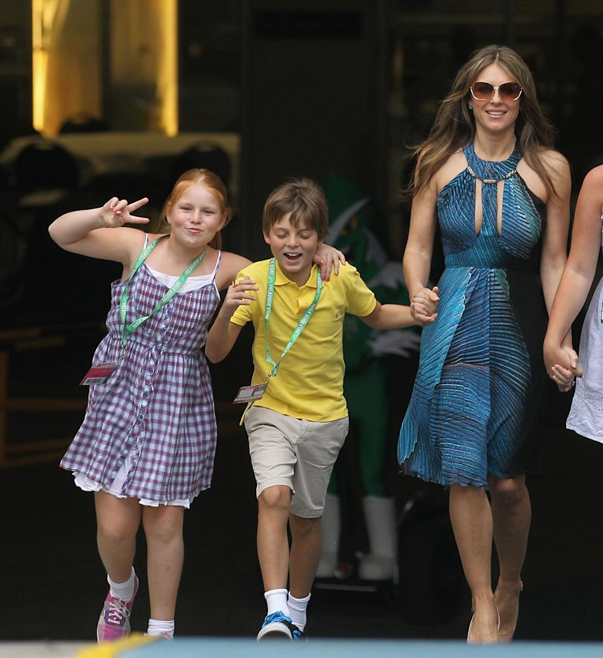 MELBOURNE, AUSTRALIA - DECEMBER 17:  Liz Hurley walks out to toss the coin with her son Damian (yellow) and Shane Warne's daughter Summer (left) ahead of the T20 Big Bash League match between the Melbourne Stars and the Sydney Thunder at Melbourne Cricket Ground on December 17, 2011 in Melbourne, Australia.  (Photo by Hamish Blair/Getty Images)