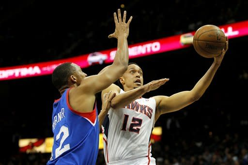 Atlanta Hawks shooting guard John Jenkins (12) shoots for two points as Philadelphia 76ers small forward Evan Turner (12) defends in first-half action of an NBA basketball game on Wednesday, March. 6, 2013, in Atlanta. (AP Photo/Todd Kirkland)