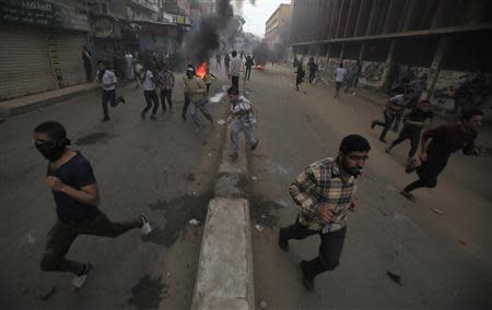 Supporters of the Muslim Brotherhood and ousted Egyptian President Mohamed Mursi flee and run near burning tyres, from tear gas fired by riot police and army, during clashes at El-Talbyia near Giza square, south of Cairo, November 29, 2013. REUTERS/Amr Abdallah Dalsh