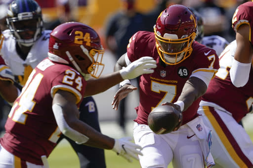 Washington Football Team quarterback Dwayne Haskins (7) hands the ball to Washington Football Team running back Antonio Gibson (24) against the Baltimore Ravens during the first half of an NFL football game, Sunday, Oct. 4, 2020, in Landover, Md. (AP Photo/Susan Walsh)
