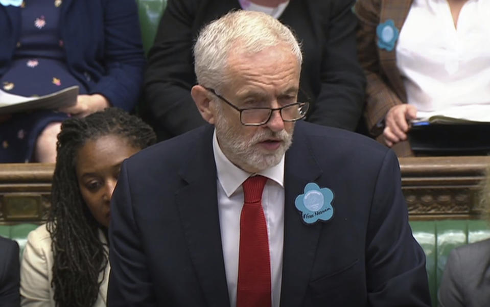 """Britain's main opposition Labour Party leader Jeremy Corbyn wears a """"Free Nazanin"""" badge as he speaks during Prime Minister's Questions session at the House of Commons in London, Wednesday June 26, 2019.  Nazanin Zaghari-Ratcliffe is a British-Iranian dual citizen who has been imprisoned in Iran for over three years. (House of Commons TV / PA via AP)"""