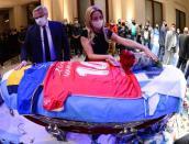 Argentina's first lady Fabiola Yanez places flowers on the casket of soccer legend Diego Maradona as Argentina's President Alberto Fernandez looks on, at the presidential palace Casa Rosada, in Buenos Aires