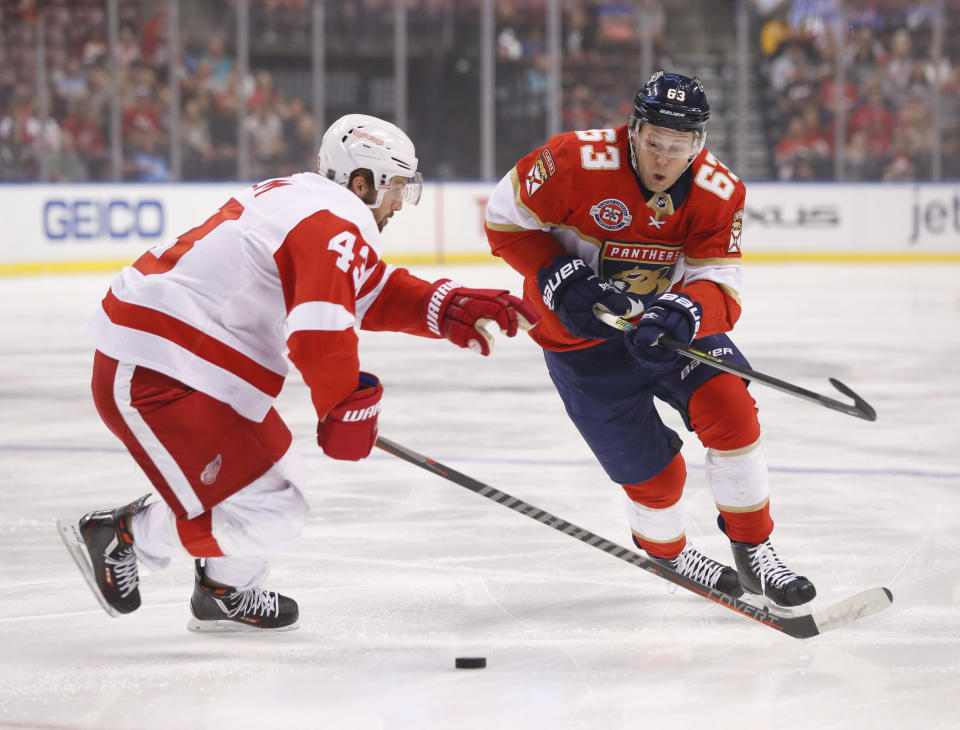 Florida Panthers right wing Evgenii Dadonov (63) and Detroit Red Wings left wing Darren Helm (43) battle for the puck during the first period of an NHL hockey game, Sunday, March 10, 2019, in Sunrise, Fla. (AP Photo/Wilfredo Lee)