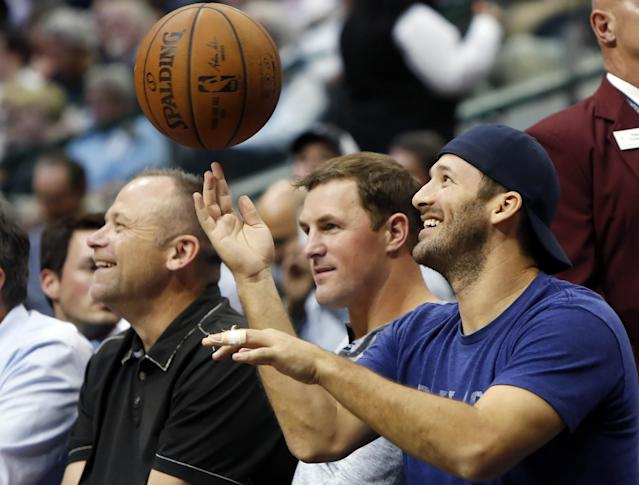 Tony Romo spins a basketball on his finger during a timeout at a March 2015 game between the Dallas Mavericks and San Antonio Spurs. (AP)