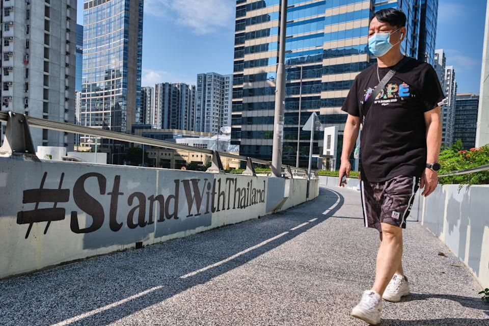 """A man wearing a face mask walks past """"#StandWithThailand"""" graffiti in Hong Kong on Oct. 18, 2020.<span class=""""copyright"""">Photo by Isaac Wong/SOPA Images/LightRocket via Getty Images</span>"""
