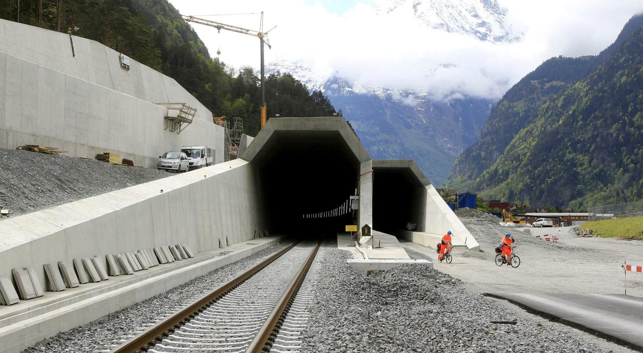 Workers cycle past the northern entrances of the NEAT Gotthard Base tunnel near Erstfeld May 7, 2012. Crossing the Alps, the world's longest train tunnel should become operational at the end of 2016. The project consists of two parallel single track tunnels, each of a length of 57 km (35 miles)     REUTERS/Arnd Wiegmann   (SWITZERLAND - Tags: BUSINESS CONSTRUCTION EMPLOYMENT TRAVEL)