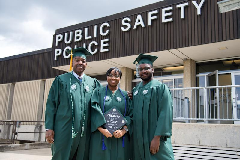 Pat(left), the fahter, poses with his son and daughter, Regan and Ryan, in front of the Eastern Michigan University Public Safety Department where he worked for 20 years. (Credit: Eastern Michigan University)