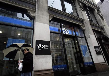 A man walks past the Time Warner Cable headquarters in New York
