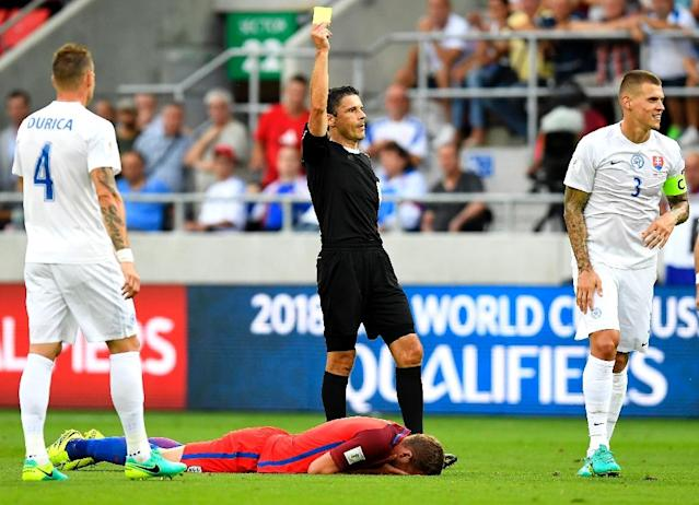Slovakia's Martin Skrtel (R) receives his first yellow card in the second half for catching Harry Kane with a flailing arm (AFP Photo/Joe Klamar)