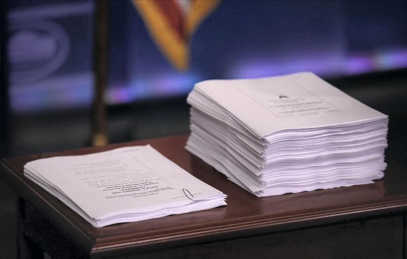 Repeal and replace recommendations produced by Republicans in U.S. House sit next to the Affordable Care Act at White House briefing