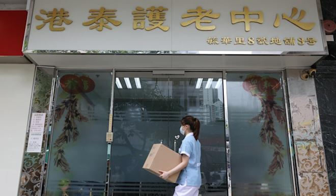 A worker carries a box outside Hong Kong's Kong Tai Care for the Aged Centre, where an 85-year-old woman was confirmed to have contracted Covid-19 on July 7. Photo: K. Y. Cheng