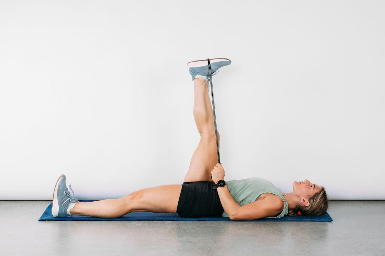 <p>Lying faceup, loop a strap around your right foot. Gently pull your right leg up toward the ceiling then toward your chest until you feel a light stretch along the back. Hold for 30 seconds, then switch sides. </p>