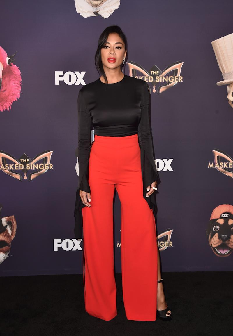 Nicole Scherzinger posing wearing a black long-sleeved top and red pants