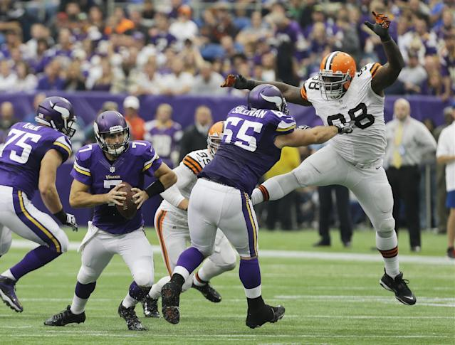 Minnesota Vikings quarterback Christian Ponder, left, runs to avoid the rush by Cleveland Browns nose tackle Phillip Taylor, right, as he is blocked by Minnesota Vikings center John Sullivan (65) during the first half of an NFL football game Sunday, Sept. 22, 2013, in Minneapolis. (AP Photo/Ann Heisenfelt)
