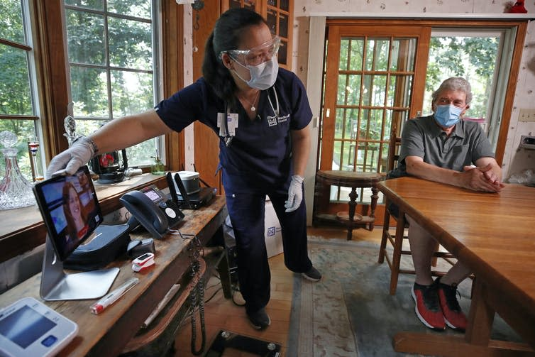 A nurse setting up a telehealth appointment for an older man in his home.