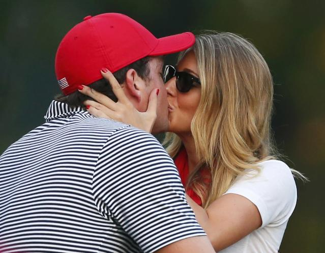U.S. golfer Keegan Bradley gets a kiss from his girlfriend Jillian Stacey after he and teammate Phil Mickelson defeated the International team of Jason Day, of Australia, and Graham DeLaet, of Canada, during the Foursome matches for the 2013 Presidents Cup golf tournament at Muirfield Village Golf Club in Dublin, Ohio October 4, 2013. REUTERS/Chris Keane (UNITED STATES - Tags: SPORT GOLF)