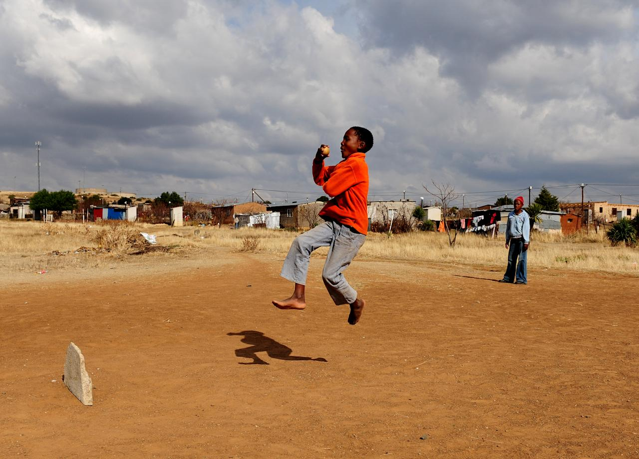 BLOEMFONTEIN, SOUTH AFRICA - JUNE 21:  A young boy bowls while enjoying a game of cricket with his friends on June 21, 2009 in Botshabelo near Bloemfontein, South Africa. The large black settlement of Botshabelo, set up by the then apartheid government, has a population of about one million inhabitants.  (Photo by Jasper Juinen/Getty Images)