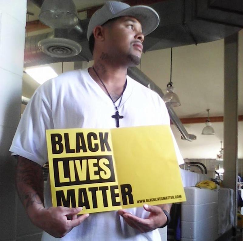 Jason Jones poses with a Black Lives Matter sign inside San Quentin State Prison. (Courtesy: Jason Jones)