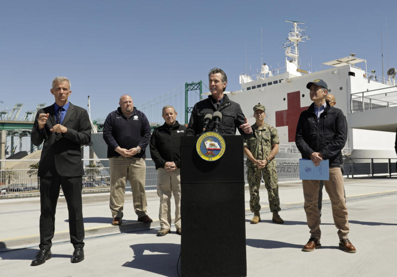 California Governor Gavin Newsom speaks in front of the hospital ship US Naval Ship Mercy that arrived into the Port of Los Angeles on Friday, March 27, 2020, to provide relief for Southland hospitals overwhelmed by the coronavirus pandemic. Also attending the press conference and keeping appropriate distancing are Los Angeles Mayor Eric Garcetti, right, Dr. Mark Ghaly, Secretary of Health and Human Services, behind Garcetti, Director Mark Ghilarducci, Cal OES, third left, Robert Fenton, FEMA Regional Administrator for Region 9, second left, U.S. Navy Admiral John Gumbleton, third right, and interpreter Richard Pope, left. (Carolyn Cole/Los Angeles Times via AP, Pool)