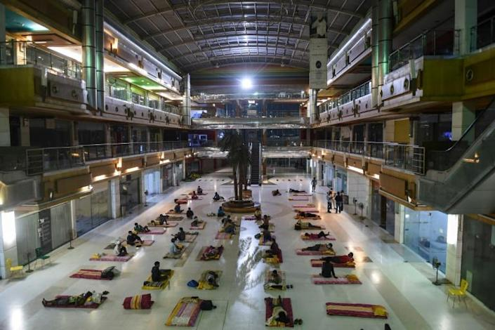 Migrant workers bed down at the shuttered JP Iscon mall in Ahmedabad, India (AFP Photo/SAM PANTHAKY)