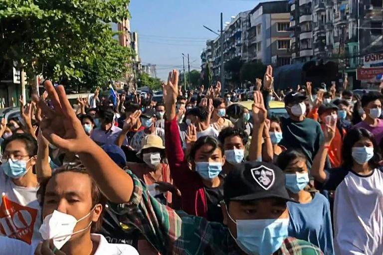 Protesters make a three-finger salute as they take part in a flash mob as part of demonstrations against the military coup in Yangon