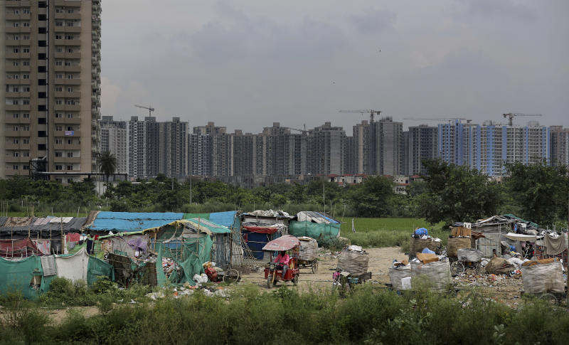 In this Thursday, Sept. 5, 2019, photo, an Indian man drives a battery operated rickshaw through a slum as unfinished residential housing projects are seen in the background in Noida on the outskirts of New Delhi, India. India's economy, once one of the fastest growing in the world, is braking in a blow to the labor-intensive manufacturing sector. Growth slipped to 5% in the April-June quarter, the slowest pace in six years, and many economists believe that Prime Minister Narendra Modi's signature economic policies are at least partly to blame. (AP Photo/Altaf Qadri)