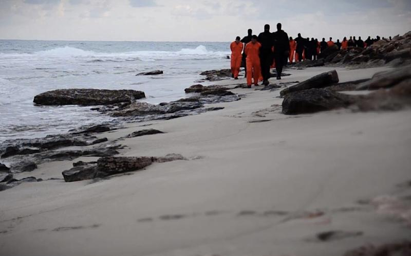 Black-clad Islamic State group fighters leading handcuffed hostages, said to be Egyptian Coptic Christians, to their deaths in Libya in February
