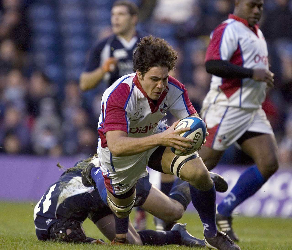 FILE - In this Nov. 18, 2006, file photo, Pacific Islands' Dan Leo prepares to score a try during their Autumn Test series match against Scotland at Murrayfield Stadium, Edinburgh, Scotland. The treatment of Pacific Island rugby players in the professional era is compared to colonialism in a new documentary film produced and narrated by former Samoa international Leo. (AP Photo/Ian Stewart, File)