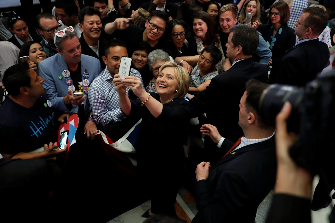 Democratic U.S. presidential candidate Hillary Clinton take a selfie with supporters during a campaign event in San Francisco, California, U.S. May 26, 2016. REUTERS/Stephen Lam     TPX IMAGES OF THE DAY