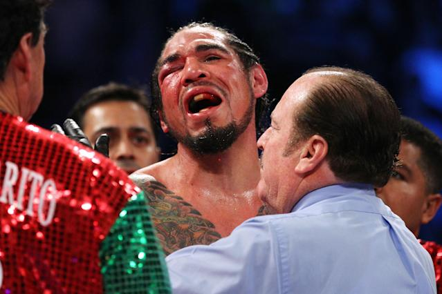 Antonio Margarito reacts after referee Steve Smoger (R) calls the fight due to Margarito's closed right eye against Miguel Cotto in the 10th round of their junior middleweight title fight on Dec. 3, 2011, at Madison Square Garden. (Photo by Al Bello/Getty Images)