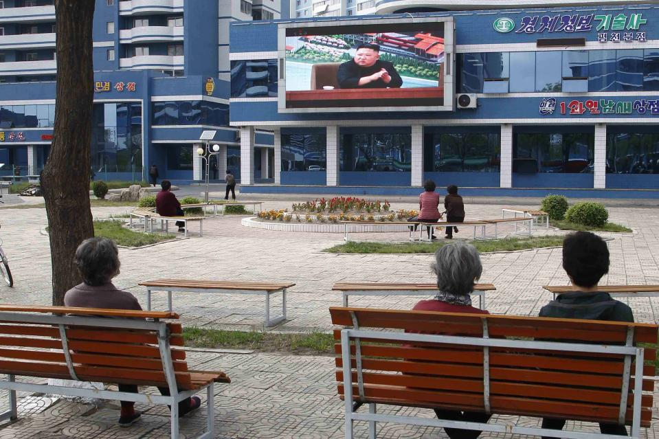 People in a park watch news broadcasted on a giant screen showing leader Kim Jong Un attending the opening ceremony of the Sunchon Phosphatic Fertilizer Factory Saturday, May, 2nd. 2020, in Pyongyang, North Korea. Un made his first public appearance in 20 days as he celebrated the completion of a fertilizer factory near Pyongyang, state media said Saturday, ending an absence that had triggered global rumors that he may be seriously ill. (AP Photo/Cha Song Ho)