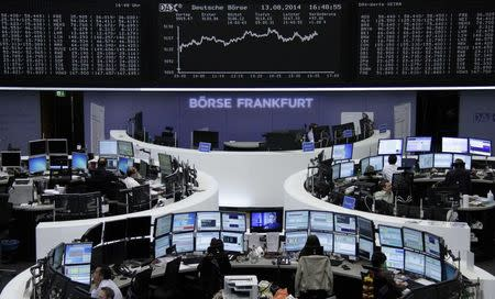 Traders are pictured at their desks in front of the DAX board at the Frankfurt stock exchange August 13, 2014. REUTERS/Remote/Stringer