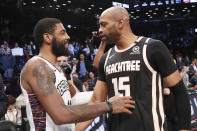 Brooklyn Nets guard Kyrie Irving (11) talks with Atlanta Hawks guard Vince Carter (15) during the second half of an NBA basketball game, Sunday, Jan. 12, 2020, in New York. The Nets defeated the Hawks 108-86. It was Irving's first time back on the court in a game since his shoulder injury in November 2019, and it was Carter's last game as a visiting player at the Barclays Center. Carter is one of the most popular Nets players. (AP Photo/Kathy Willens)