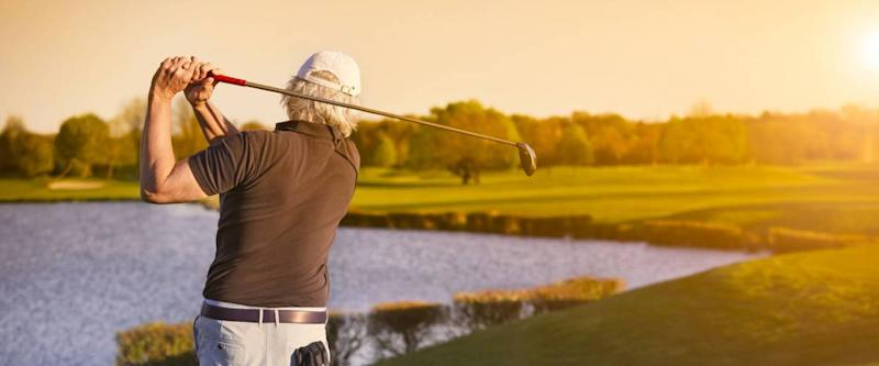 Senior golf player shooting ball at sunset