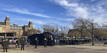 Dutch riot police line up in front of the Rijksmuseum, rear left, as they watch over a demonstration against the curfew and other COVID-19 related restrictions aimed at curbing the spread of the coronavirus, in Amsterdam, Netherlands, Sunday, Jan. 31, 2021. (AP Photo/Mike Corder)