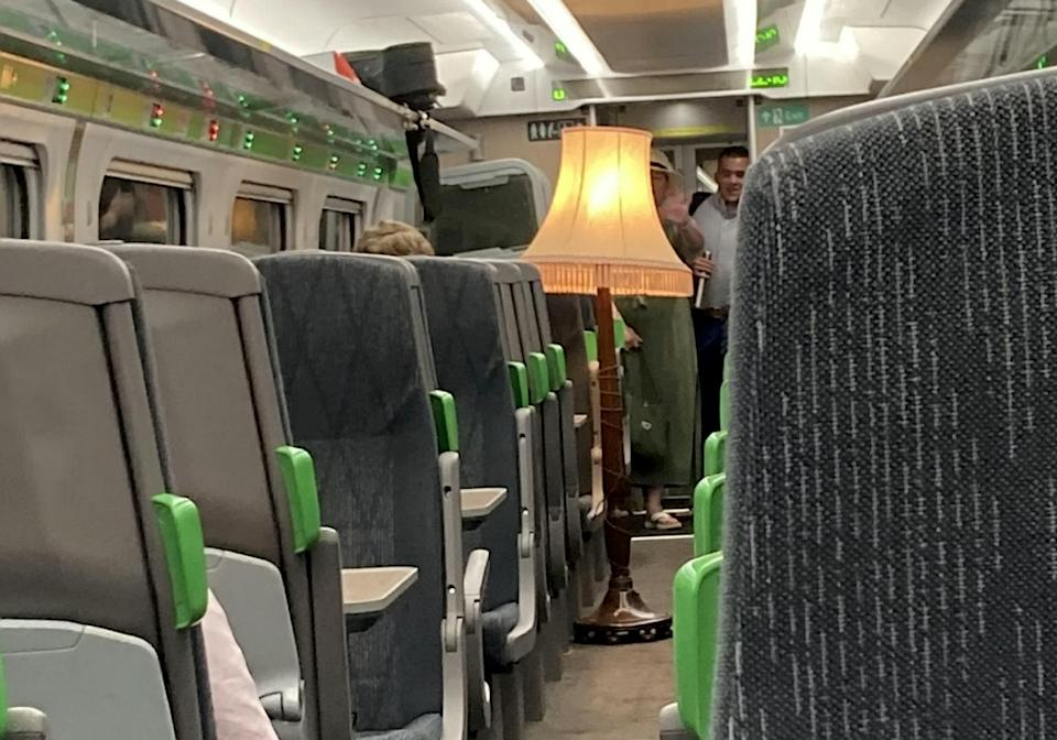 The man boarded a train and plugged in a giant old fashioned lamp in the middle of the aisle.  (SNWS)