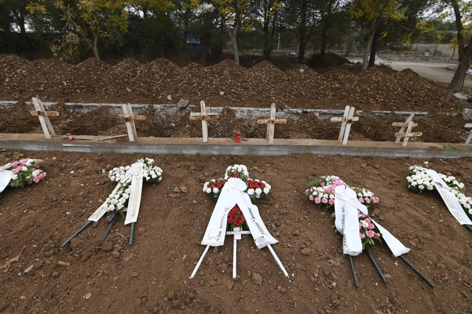 Wreaths lie atop the new graves of recent fatalities of the coronavirus pandemic in the northern city of Thessaloniki, Greece, on Wednesday, Dec. 2, 2020. Greece has been battling a resurgence of the virus that has led to record numbers of daily deaths. A nationwide lockdown imposed in early November has been extended until Dec. 7. (AP Photo/Giannis Papanikos)