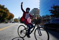 A woman rides her bike as she takes part in a protest the day after the 2020 U.S. presidential election in Washington