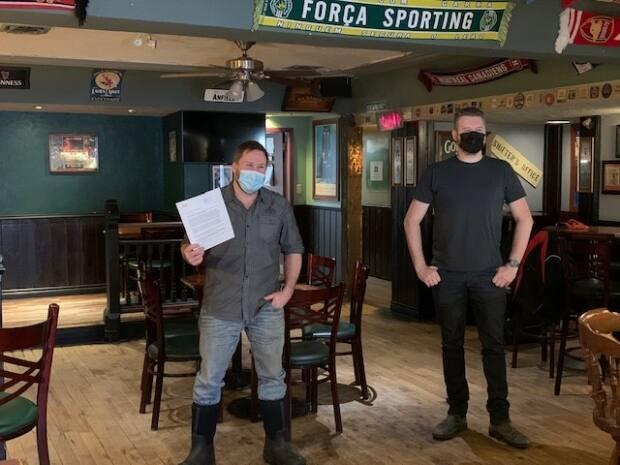 Trevor Sinclair stands beside Patrick Jacobson at the Black Knight. Sinclair holds the letter MusicNWT sent to the Office of the Chief Public Health Officer supporting Jacobson and his calls for set rules when it comes to performing.
