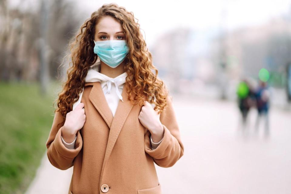 Woman wearing face mask standing on a street.