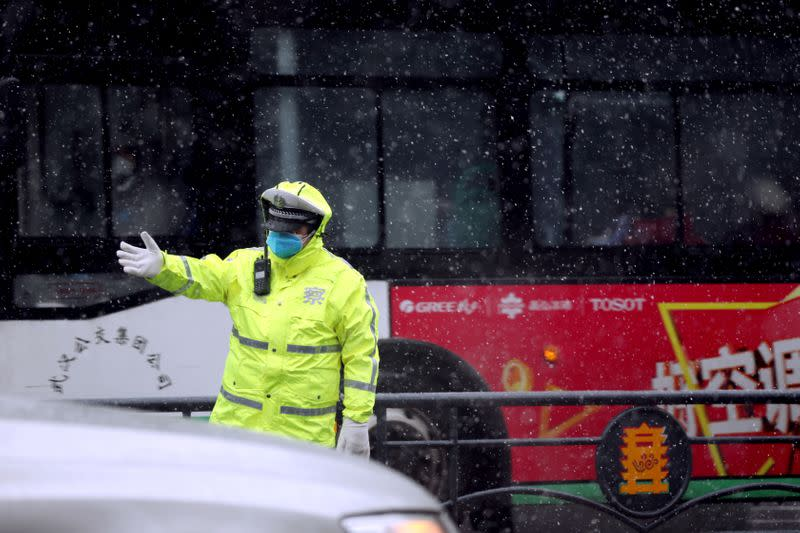 Police officer directs the traffic amid snowfall in Wuhan, the epicentre of the novel coronavirus outbreak