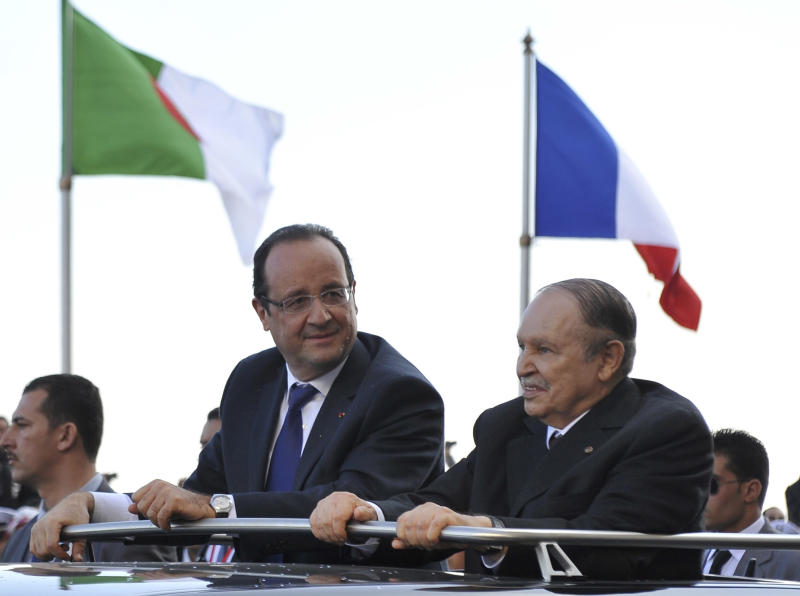 French President Francois Hollande, left, and Algerian President Abdelaziz Bouteflika stand in a car as they drive through Algiers Wednesday, Dec.19, 2012. Hollande arrived Wednesday on a state visit to Algeria, hoping for a clean start in relations after a half-century of tensions with this North Africa nation, once the French empire's most prized colony. (AP Photo/Anis Belghoul)