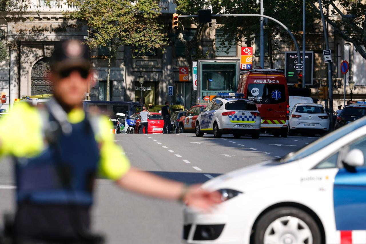 <p>A policemen stand as he blocks the street to a cordoned off area after a van ploughed into the crowd, injuring several persons on the Rambla in Barcelona on August 17, 2017. (Pau Barrena/AFP/Getty Images) </p>