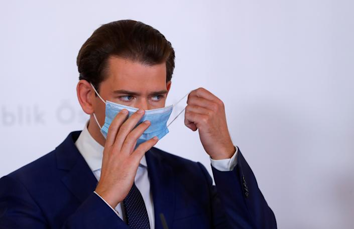 Austria's Chancellor Sebastian Kurz takes off his mask as he attends a news conference, as the spread of the coronavirus disease (COVID-19) continues, in Vienna, Austria October 31, 2020. REUTERS/Leonhard Foeger