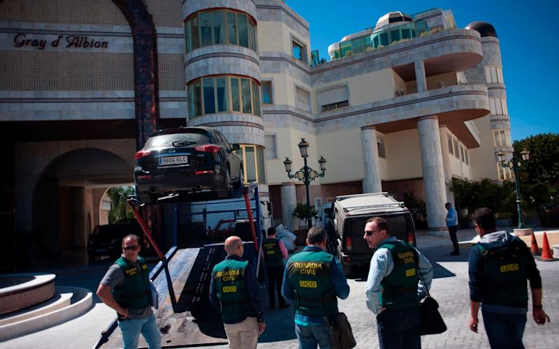 Members of the Spanish Guardia civil stand near vehicles seized during a raid targeting assets of the family of Syrian leader Bashar al-Assad - AFP