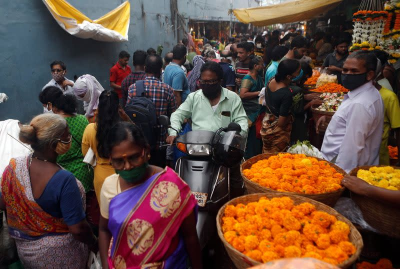 FILE PHOTO: A man rides a scooter at a crowded market a day before the Hindu festival of Dussehra amidst the spread of the coronavirus disease (COVID-19) in Mumbai
