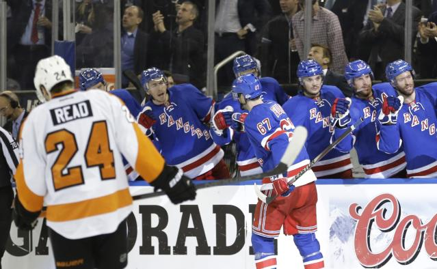 Philadelphia Flyers right wing Matt Read (24) skates away as New York Rangers' Benoit Pouliot (67) celebrates with teammates after scoring a goal during the second period in Game 7 of an NHL hockey first-round playoff series on Wednesday, April 30, 2014, in New York. (AP Photo)