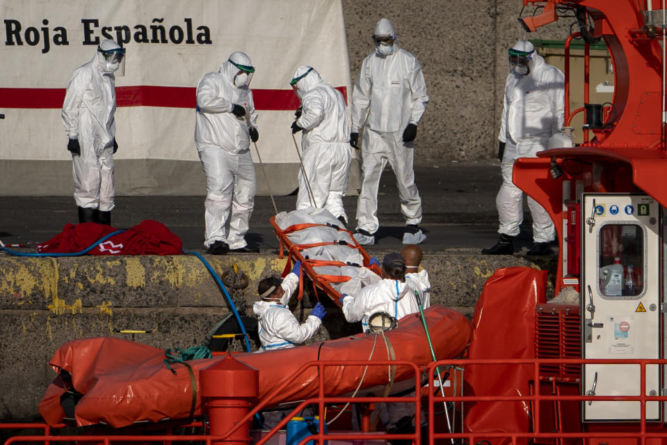 Emergency workers carry a migrant's body after being found dead by the Spanish Maritime Rescue Service, at the Arguineguin port in Gran Canaria island, Spain, on Friday, Aug. 21, 2020. Spanish authorities say that five migrants have died and 11 survived while trying to reach the Canary Islands, bringing to 20 the number of people who have lost their lives that week in the perilous migration route to Europe. (AP Photo/Emilio Morenatti)
